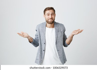 So what, Who cares. Unsure doubtful stylish european bearded man wearing jacket shrugging his shoulders in questioning gesture of uncertainty and having regretful clueless look