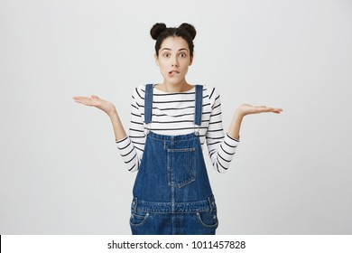 So what, Who cares. Unsure doubtful stylish brunette young woman wearing denim clothes shrugging shoulders in questioning gesture of uncertainty, biting lower lip, having regretful clueless look