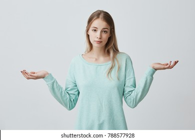 So what, Who cares. Unsure doubtful puzzled european woman with blonde dyed hair shrugging her shoulders in questioning gesture of uncertainty and having confused clueless look