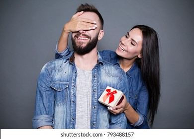 And what will happen now? A beautiful smiling woman with a gift in her hand makes a surprise to her husband and closes his eyes with his hand against a gray background. Valentine's Day.
