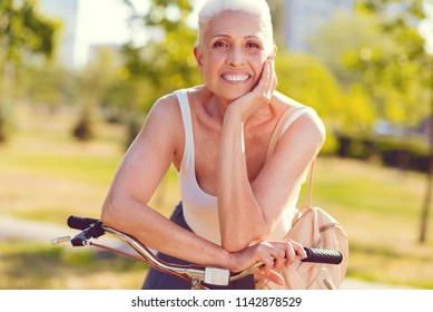 What a wonderful life. Waist up shot of an elderly lady of heavenly beauty resting her chin on a hand while standing in a park and smiling after bicycling outdoors.