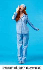 What wonderful morning. Full-length vertical studio shot yawning cute caucasian redhead girl in sleep mask and pyjama, stretching and cover opened mouth with closed eyes, blue background