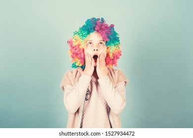 What a wonderful surprise. Surprised little girl wearing clown wig hair. Cute small girl opened mouth with big surprise. Adorable little child with surprise face. Looking with surprise.