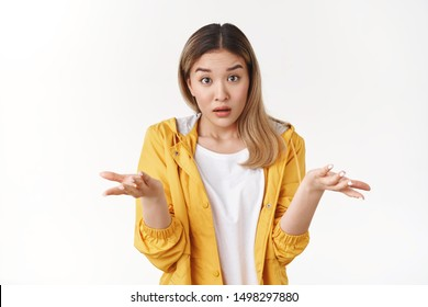 What wrong. Ambushed shocked confused young asian girl coworker shrugging hands spread sideways full disbelief asking question questioned perplexed understood situation, white background