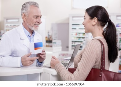 What you need. Senior joyful male pharmacist carrying drug while talking to client