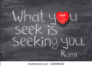 What you seek is seeking you - ancient Persian poet and philosopher Rumi quote written on chalkboard with red heart symbol instead of O