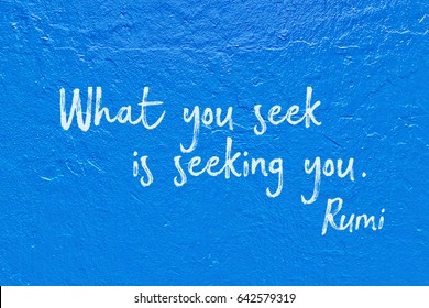 What you seek is seeking you - ancient Persian poet and philosopher Rumi quote handwritten on blue wall