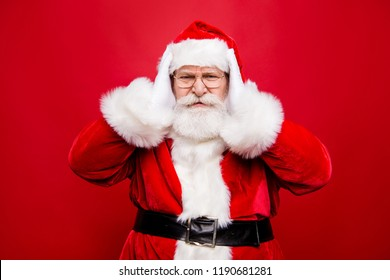 What you talk about?! I dont want hear it! Mature stylish aged white beard Santa covering ears with palm hands from loud irritated annoyed noise and offal sound isolated on noel red background