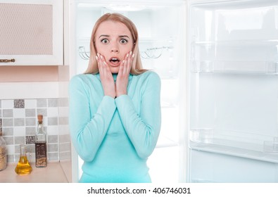 What's for dinner? Pretty blonde standing near open empty fridge. Surprised young woman looking at camera