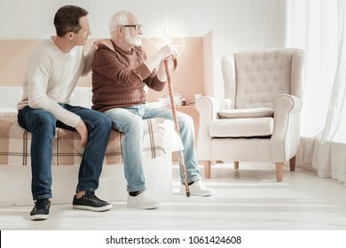 Whats wrong. Sad unhappy aged man sitting on the bed with a son having bad mood and looking aside.