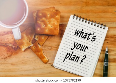 WHAT'S YOUR PLAN? inscription on a note pad with coffee morning over wooden table.