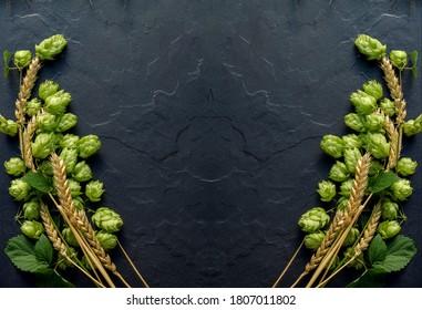 Weißbier-Konzept, Hintergrund. Hopfen- und Weizenähren sind symmetrisch auf der schwarzen Steinoberfläche angeordnet. Oktoberfest Vorlage mit Kopienraum.