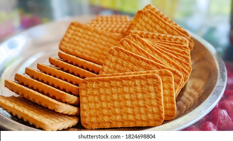 Wheat biscuits in the steel plate with blury background. Indian biscuits popularly known as Chai-biscuit in India