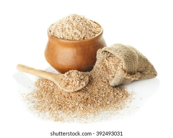 Wheat bran in bowl and a bag, a wooden spoon isolated on a white background closeup