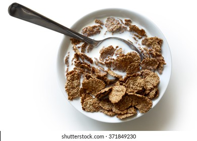Wheat bran breakfast cereal with milk and spoon in ceramic bowl. Isolated on white from above.