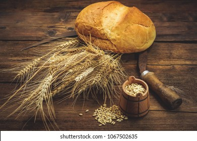 wheat bread and ears on a wooden background.