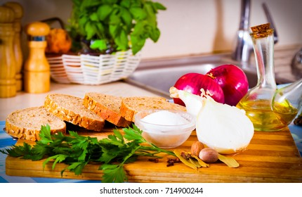 Wheat bread, salt, onions and parsley lying on a wooden cutting board