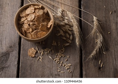 Wheat corn and oat flakes on a wooden table