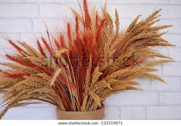 Wheat and dry flowers in a vase with background white brick wallpaper