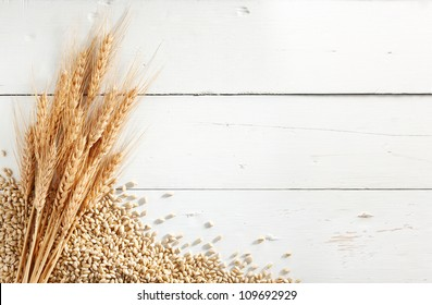 wheat ears with wheat kernels against white wood background