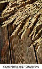Wheat ears on brown wooden background