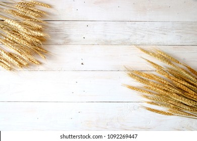 Wheat ears on rustic white wooden background