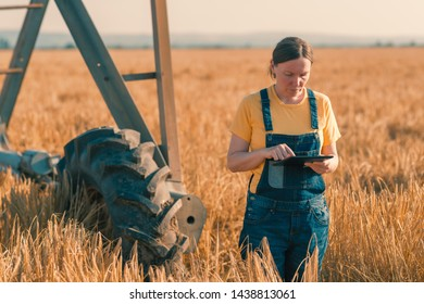 Wheat farmer using tablet in cereal crop field with irrigation equipment. Female agronomist using modern technology in farming agricultural activity.