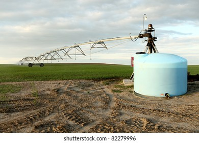 A wheat field irrigated with a center pivot sprinkler system.  It is viewed from the pivot end, and shows a mix tank with ag chemicals ready to be combined with the irrigation water.