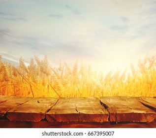 Wheat field with wood planks. Empty tabletop. Table with wheat.Beautiful Nature Sunset Landscape. Rural Scenery with golden wheat. Agriculture background with Harvest