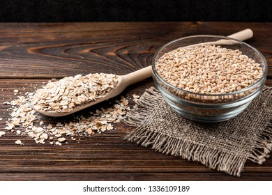 Wheat and flakes on dark wooden background.