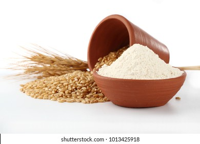 Wheat flour Bunch of wheat ears, dried grains in terracota bowl, flour in terracota  bowl    on white background. Cereals harvesting, bakery products