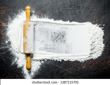 Wheat flour with rolling pin. On dark rustic background