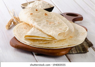 Wheat Flour Tortillas on wooden board. Selective focus