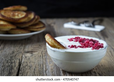Wheat golden pancakes with sour cream and raspberries. Closeup view