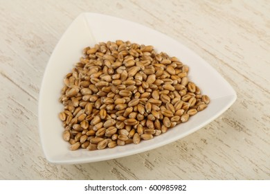 Wheat grains in the bowl over wooden background