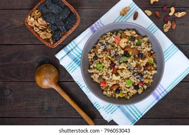 Wheat porridge with nuts, dried berries, raisins, poppies in a ceramic bowl on a dark wooden background. Proper nutrition. Healthy food. The top view
