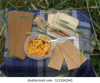 Wheat products displayed on a blue plaid tablecloth in a wheat field