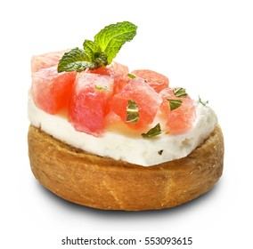 wheat rusk called ntakos in Greece, topped with a slice of cyprian cheese, mint leaves and watermelon cubes