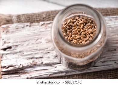 Wheat seeds in a glass jar on a white rustic board side view horizontal