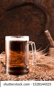 Wheat table beer in a glass, sickle, rusty background