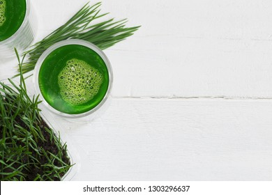 Wheatgrass fresh juice and  green wheatgrass plants isolated on white wooden background, copy space on the right side