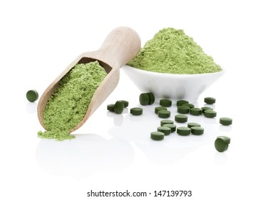 Wheatgrass powder, green chlorella and spirulina pills isolated on white background with reflection. Healthy living. Organic natural food supplement.