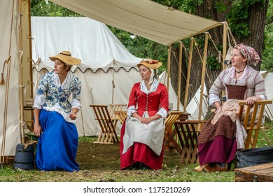WHEATON, ILLINOIS/USA - SEPT. 8, 2018: Three young women in period dress watch a demonstration (off camera) in a military encampment at a reenactment of the American Revolutionary War (1775-1783).