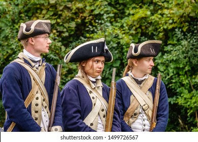 WHEATON, IL/USA - SEPT. 7, 2019: Three young Continental soldiers in uniform, a man and two women, watch fifers (off camera) perform at a reenactment of the American Revolutionary War (1775-1783).