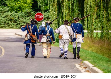 WHEATON, IL/USA - SEPT. 7, 2019: Side by side, four comrades in arms follow a woman reenactor along a service road after a skirmish at a reenactment of the American Revolutionary War (1775-1783).