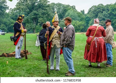 WHEATON, IL/USA - SEPT. 8, 2018: Two men in military uniform and a woman in period dress mingle with visitors at a reenactment of the American Revolutionary War (1775-1783) at Cantigny Park.