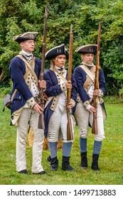 WHEATON, IL/USA - SEPT. 8, 2019: Three Continental soldiers in uniform, a young man and two young women, perform a drill together at a reenactment of the American Revolutionary War (1775-1783).