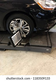 Wheel alignment in a black car. Maintenance operation for wheels in the automobile