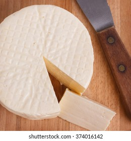 Wheel of brazilian traditional cheese Minas on wooden board. Selective focus