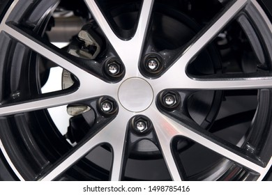 The wheel of the car is made of a metal alloy such as aluminum and magnesium, and the clean surface reflects the silver luster. It is an accessory for modern transportation wheels.